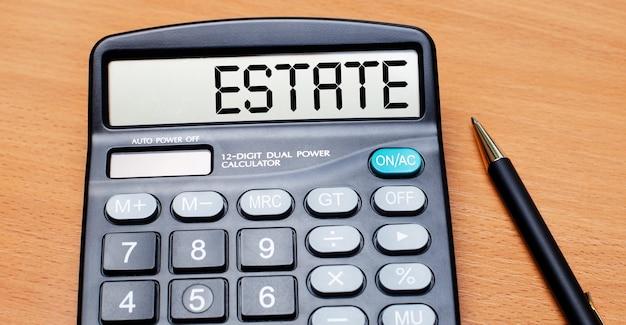 На деревянном столе черная ручка и калькулятор с надписью estate. бизнес-концепция