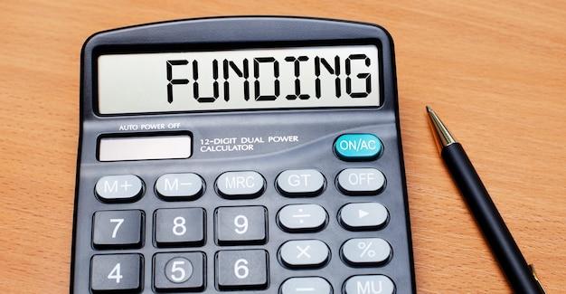 На деревянном столе есть черная ручка и калькулятор с текстом финансирование. бизнес-концепция