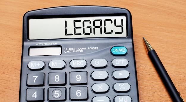 На деревянном столе черная ручка и калькулятор с текстом наследие. бизнес-концепция