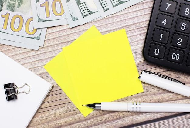 木製のテーブルには、電卓、現金、ペン、ペーパークリップ、黄色のステッカーがあり、テキストやイラストを挿入できます。レンプレート。ビジネスコンセプト