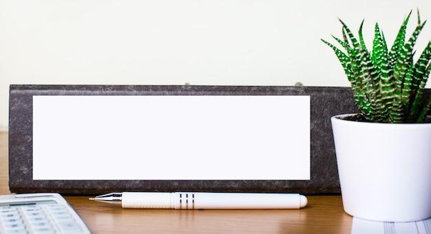 На деревянном столе - папка для документов с местом для вставки текста, зеленое растение в горшке, ручка и калькулятор. бизнес-концепция. шаблон