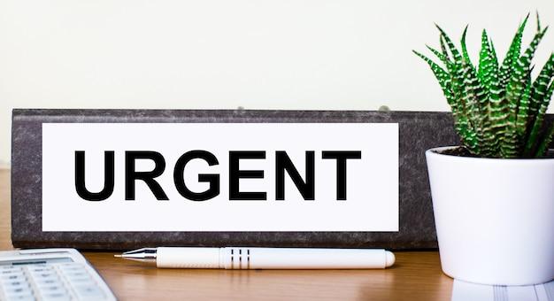 На деревянном столе папка для документов с срочным тестом, зеленое растение в горшочке, ручка и калькулятор. бизнес-концепция.