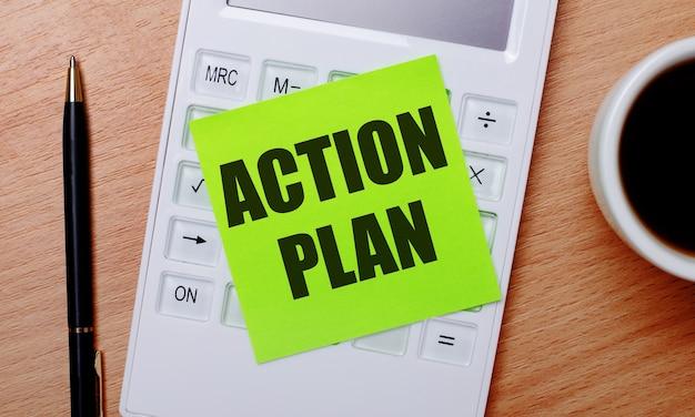 На деревянном столе ручка и калькулятор с зеленой наклейкой с текстом план действий.