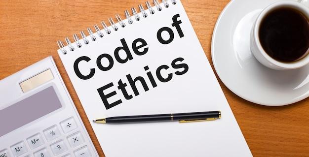 木製のテーブルには、白い電卓、白い一杯のコーヒー、ペン、そして「倫理規定」というテキストが書かれた白いノートがあります。ビジネスコンセプト
