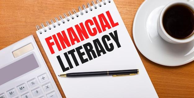 木製のテーブルには、白い電卓、白い一杯のコーヒー、ペン、そして「金融リテラシー」と書かれた白いノートがあります。ビジネスコンセプト