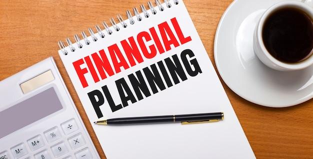 На деревянном столе белый калькулятор, белая чашка кофе, ручка и белый блокнот с текстом финансовое планирование. бизнес-концепция