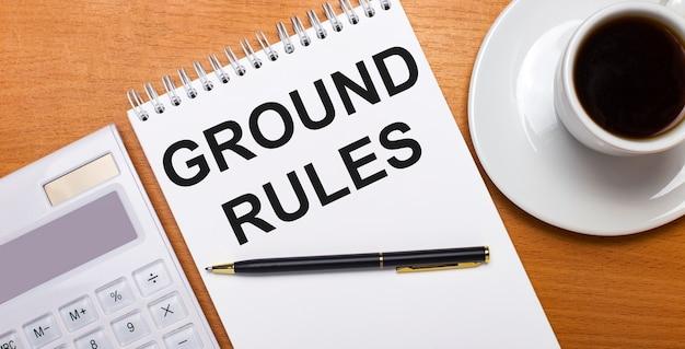 На деревянном столе стоит белый калькулятор, белая чашка кофе, ручка и белый блокнот с текстом «правила назначения». бизнес-концепция