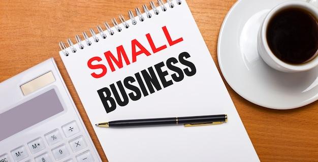 На деревянном столе белый калькулятор, белая чашка кофе, ручка и белый блокнот с текстом малый бизнес. бизнес-концепция