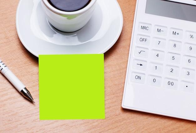 木製のテーブルには、白いコーヒー、ペン、白い電卓、テキストを挿入する場所のある緑色のステッカーがあります。テンプレート。ビジネスコンセプト