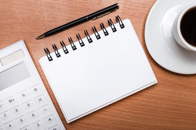 На деревянном столе стоит белая чашка кофе, белый калькулятор, ручка и белый чистый блокнот с местом для вставки текста. шаблон. бизнес-концепция