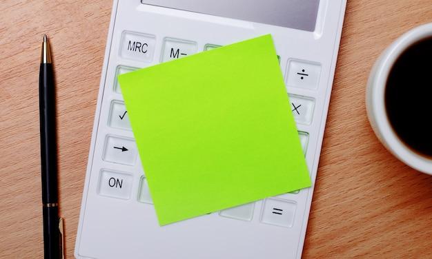 На деревянном столе кофе в белой чашке, ручка и белый калькулятор с зеленой наклейкой с местом для вставки текста. шаблон. бизнес-концепция