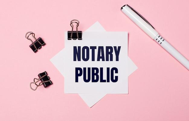 На деревянном столе кофе в белой чашке, ручка и белый калькулятор с зеленой наклейкой с надписью notary public. бизнес-концепция