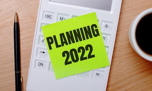 木製のテーブルには、白いカップに入ったコーヒー、ペン、緑色のステッカーが付いた白い電卓があり、「計画2022」というテキストが付いています。ビジネスコンセプト