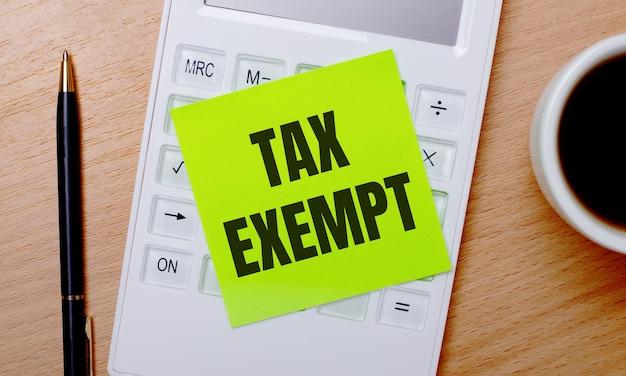 На деревянном столе кофе в белой чашке, ручка и белый калькулятор с зеленой наклейкой с надписью tax exempt. бизнес-концепция