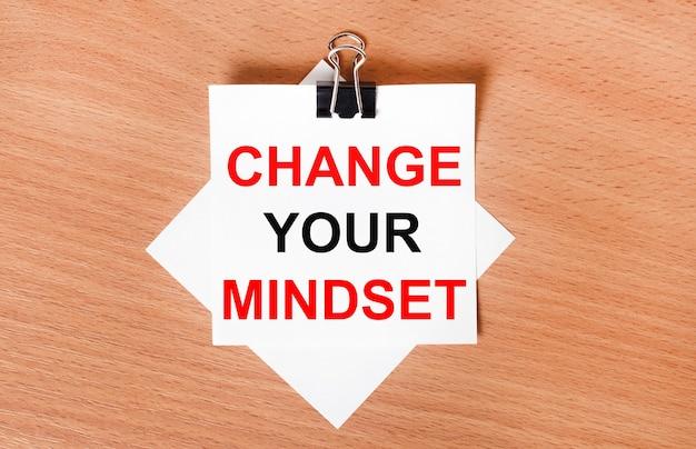 На деревянном столе под черной канцелярской скрепкой лежит лист белой бумаги с надписью измените свой мышление.