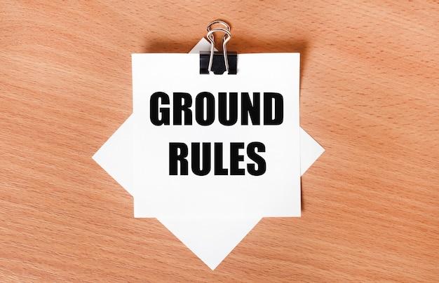 На деревянном столе под черной канцелярской скрепкой лежит лист белой бумаги с текстом основные правила.