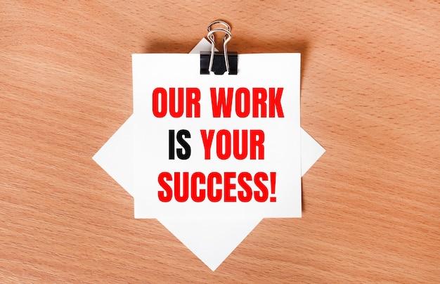 На деревянном столе под черной канцелярской скрепкой лежит лист белой бумаги с текстом наша работа - ваш успех.