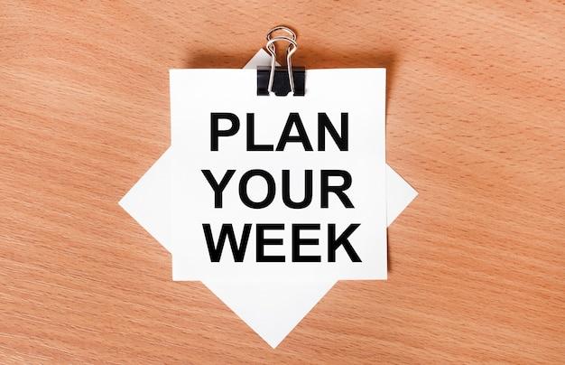 黒いペーパークリップの下の木製のテーブルの上に、「週を計画する」というテキストが書かれた白い紙が置かれています。
