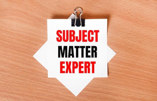 На деревянном столе под черной канцелярской скрепкой лежит лист белой бумаги с текстом subject matter expert.
