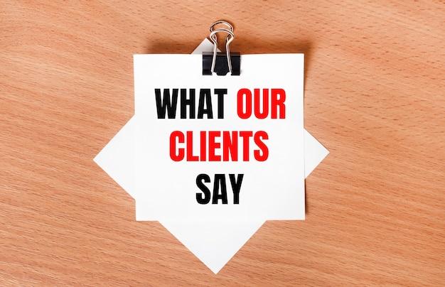 검은색 종이 클립 아래의 나무 테이블에는 what our clients say라는 텍스트가 있는 흰색 종이가 놓여 있습니다.
