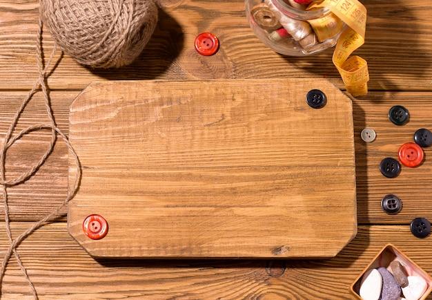 空のボードボタンとスレッドのある木製のテーブル。縫製のコンセプトです。コピースペース