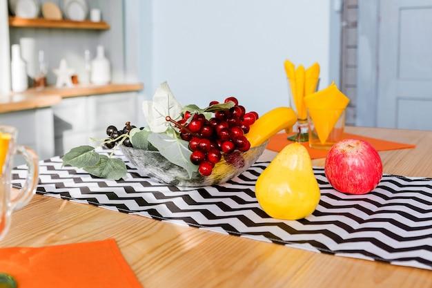 나무 탁상에는 세련된 프린트가있는 냅킨에 과일이 들어있는 인공 꽃병, 냅킨이 달린 유리 컵이 있습니다. 가로 사진