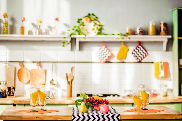 На деревянной столешнице - ваза с фруктами, стеклянные чашки с салфетками. на заднем плане - стильно оформленный кухонный интерьер. горизонтальное фото