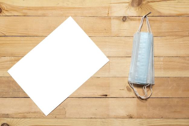 На деревянной стене на гвозде висят медицинские маски, а рядом с ними висит белый лист бумаги.