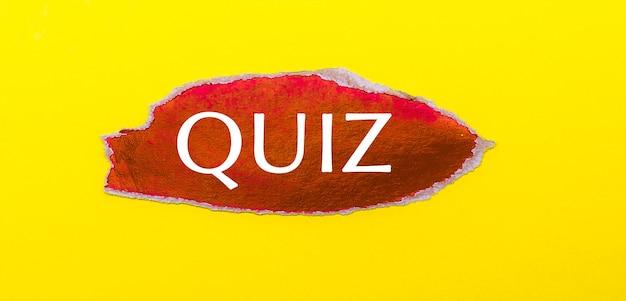 黄色の背景に、クイズという言葉が書かれた赤い紙のシート