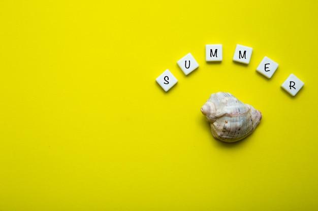 노란색 배경에는 껍데기가 있고 그 위에 여름이라는 단어가 쓰여 있습니다