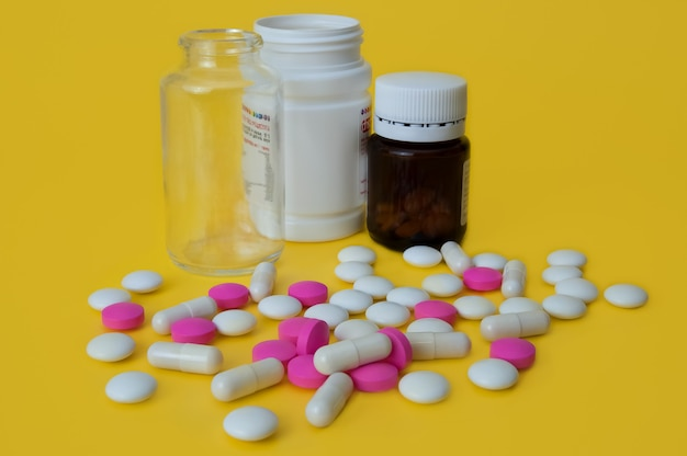 黄色の背景に白とピンクの錠剤が点在しており、ガラスとプラスチックのボトルが3本あります。側面図。