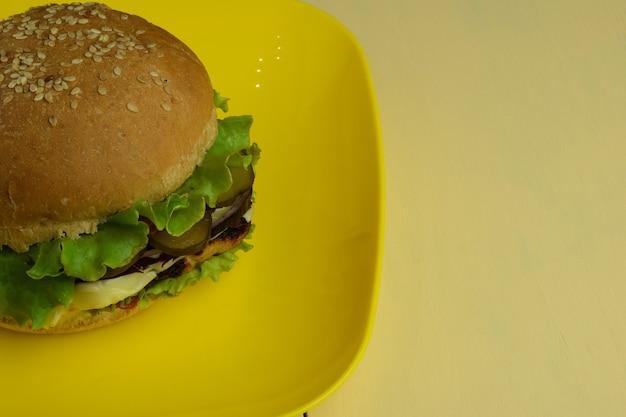 黄色いセラミックの四角いプレートの上に大きなサンドイッチがあります。プレートはベージュの木製テーブルの左側にあります