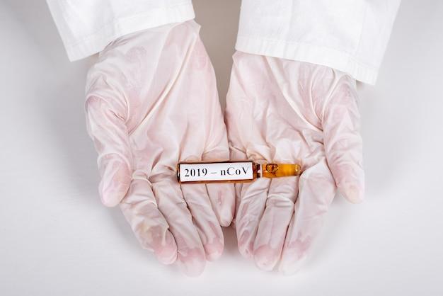 의료 노동자의 흰 장갑에 양서류에 앰플 거짓말