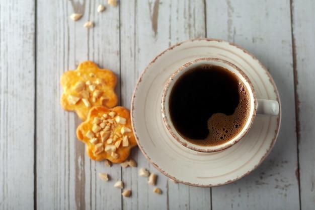 古い白い木製のテーブルの上に、香り高いコーヒーを 1 杯。