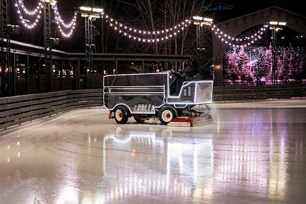 На открытом катке, освещенном праздничными огнями и гирляндами, комбайн восстанавливает лед для катания.