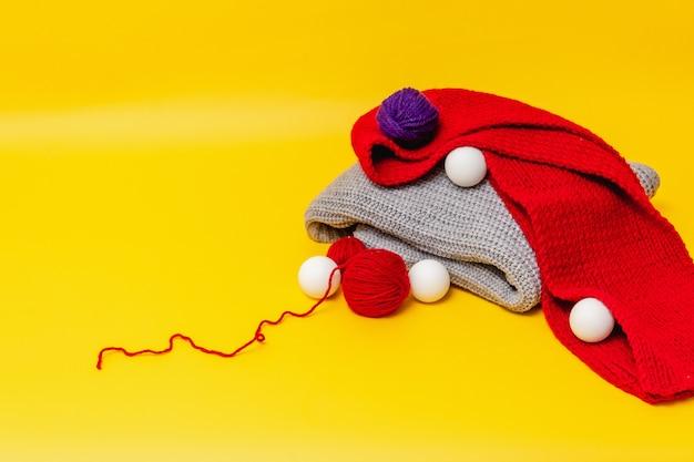オレンジ色の背景には、灰色の折り畳まれたセーターと赤いスカーフがあり、ウール糸の赤と青のボール、散らばった白いボールがあります