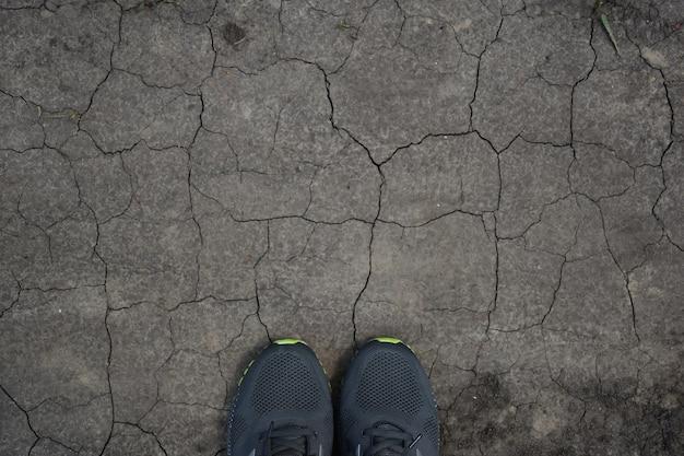 На засушливой земле, повсюду потрескавшейся внизу рамы, выглядывают две кроссовки. сверху достаточно места для надписи