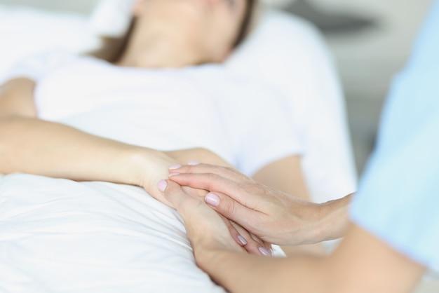ベッドの上に病気の医者が彼の隣に座って、同情的に手を握っています。安楽死