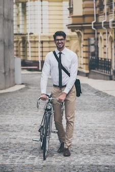 На байке куда хочу! уверенный молодой человек в очках с улыбкой смотрит в камеру и держится за руки на велосипеде во время прогулки на свежем воздухе