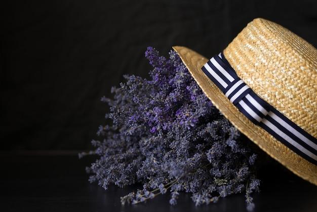 黒に帽子と弓が付いたラベンダーの大きな香りのよい花束。
