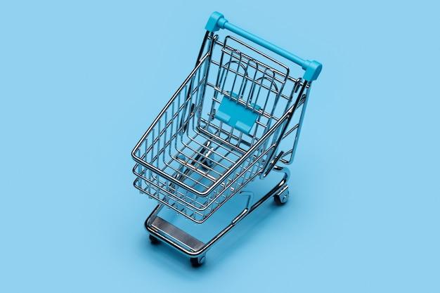 На синем фоне серебряная тележка для покупок