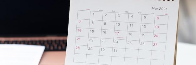 デスクトップには、ペンと紙のスケジュールの毎日のタスクの概念の横にカレンダーがあります