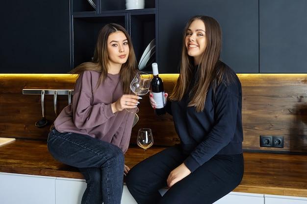 술 파티 전날, 젊은 여성들은 부엌 조리대에 앉아 와인과 잔을 들고 포즈를 취합니다.