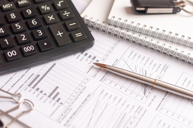 На финансовых документах со столбцами чисел стоит черный калькулятор. ручка и очки для зрения. бизнес и финансовая концепция