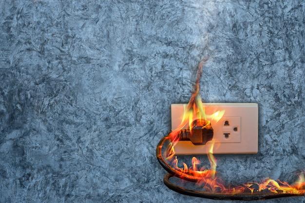 В огне электрическая вилка провода розетка на бетонной стене выставлена бетонный фон с копией пространства