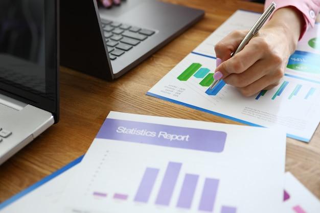 女の子の机の上にはラップトップと統計レポートがあります