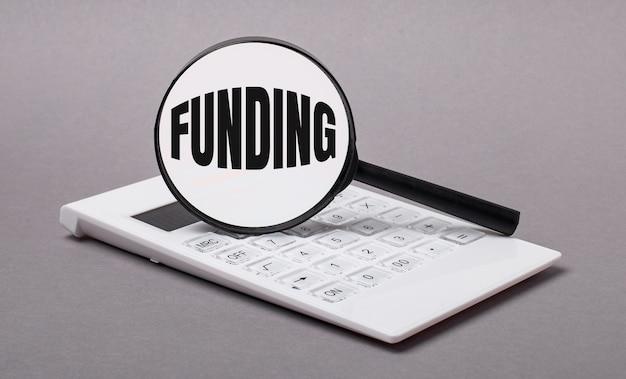 회색 배경에 검은색 계산기와 돋보기(funding) 텍스트가 있습니다. 비즈니스 개념