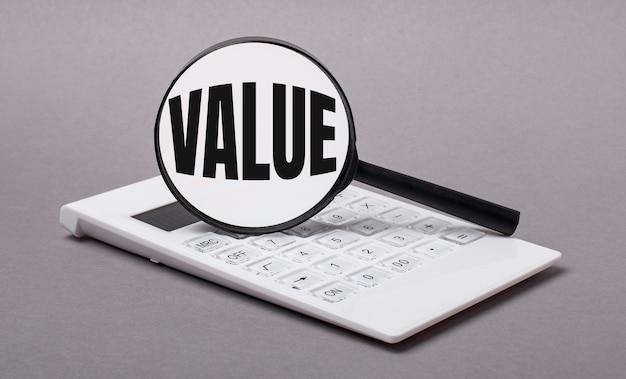 На сером фоне черный калькулятор и лупа с текстом value. бизнес-концепция