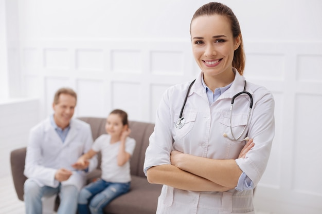 あなたの健康を守るために。彼女の同僚が注射の成功後に彼女の小さな患者を慰めている間、彼女のオフィスでポーズをとっている魅力的な楽しいプロの医者