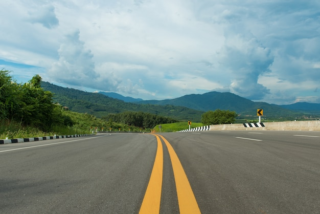 丘のアスファルトの道路と青空自然風景